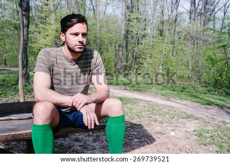 Handsome man in park, workout, resting on the bench