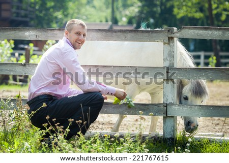 handsome man in pink shirt play with white pony horse on green field country farm - stock photo