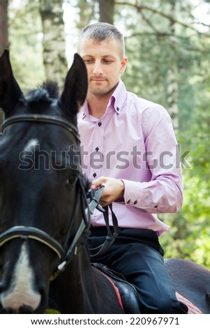 handsome man in pink shirt ride on the black horse in green forest