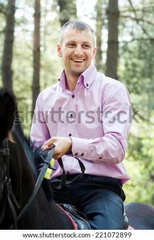 handsome man in pink shirt ride on the black horse in green forest - stock photo