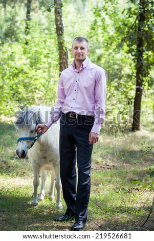 handsome man in pink shirt walk with white pony horse in green forest - stock photo