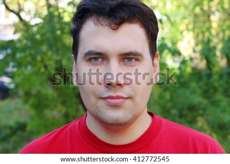Handsome man in red stands in green park at sunny day, shallow dof - stock photo