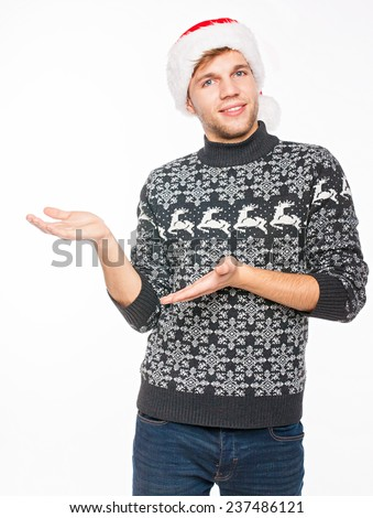 Handsome man in Santa's hat and Norwegian sweater as a presenter . Isolated on white background