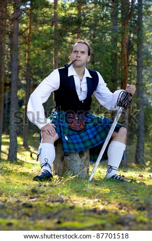 Handsome man in scottish costume with sword and pipe outdoor - stock photo