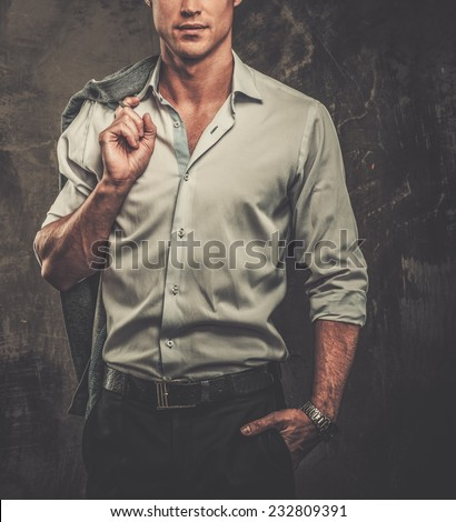 Handsome man in shirt against grunge wall holding jacket over shoulder  - stock photo