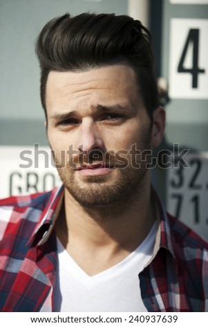 Handsome man in striped shirt and t shirt with beard and funky haircut - stock photo