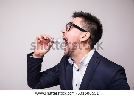 handsome man in suit  eat light bulb
