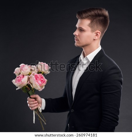 Handsome Man In Suit Holding A Bunch Of Pink Roses - stock photo