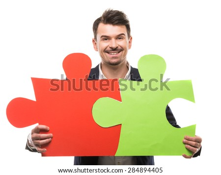 Handsome man in suit holding big puzzle. White background. - stock photo