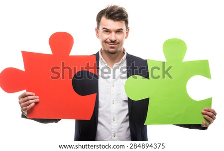Handsome man in suit holding big puzzles. White background. - stock photo