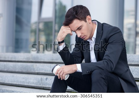 Handsome man in suit is sitting on steps and drinking coffee. He is looking down pensively and leaning his head on his arm. He is nervous. Copy space in left side - stock photo