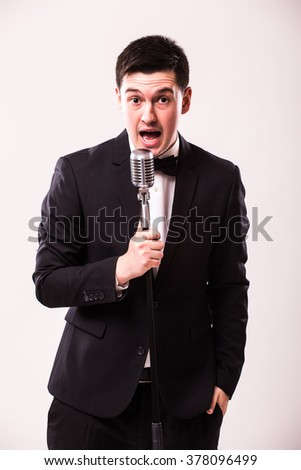 Handsome man in suit singing with the microphone and look at camera. Isolated on white background. Singer concept.