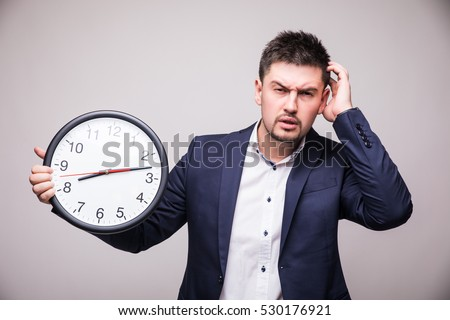 Handsome man in suit with clock in hand lose time of meeting