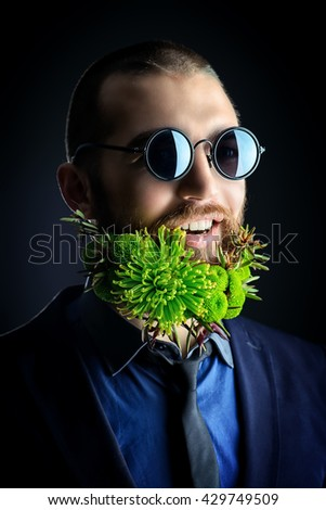 Handsome man in sunglasses and with a beard of green flowers smiling at camera. Men's beauty. Barbershop. - stock photo
