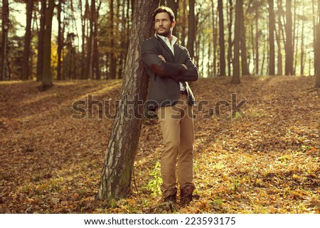 Handsome man in the park. Autumn scenery - stock photo