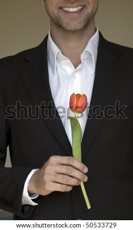 handsome man in the suit with a red tulip - stock photo