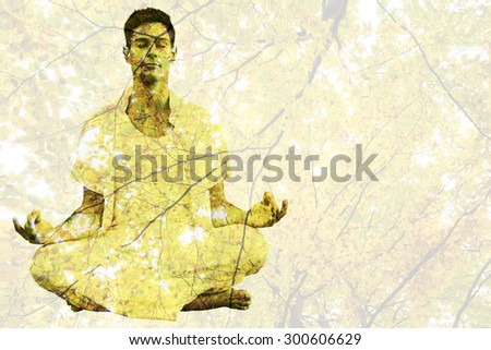 Handsome man in white meditating in lotus pose against branches and autumnal leaves - stock photo