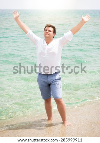 Handsome man in white shirt enjoying sea and raising hands in the sky - stock photo