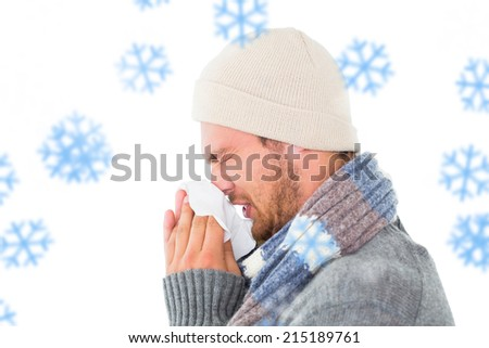 Handsome man in winter fashion blowing his nose against snowflakes - stock photo
