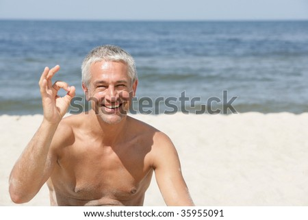 Handsome man indicating OK sign on the beach - stock photo