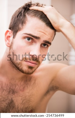 Handsome man is checking hairline while looking at the mirror. - stock photo
