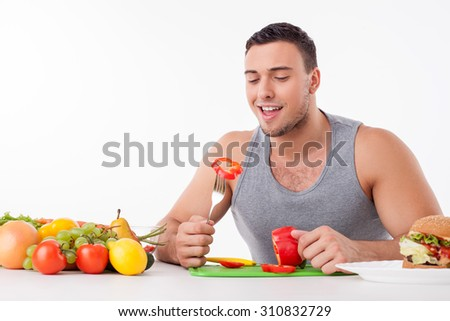 Handsome man is eating chopped pepper with enjoyment. He is sitting and the table and smiling. The man is in process of cooking a salad. Isolated on background and copy space in left side - stock photo