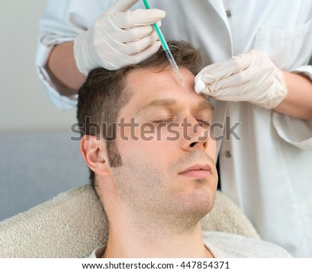 Handsome man is getting injection. Concept of aesthetic beauty. - stock photo