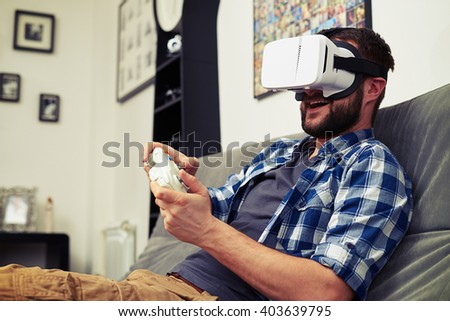 Handsome man is having fun while playing computer game with joystick and virtual reality glasses