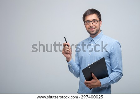 Handsome man is holding a folder and pen in his hands. He is ready to write something. The guy is looking forward with interest and smiling. Isolated on grey background and copy space in left side - stock photo