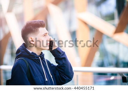 Handsome man is is using cell phone call , outdoor on the city street, Young attractive businessman wearing casual blue shirt  - stock photo