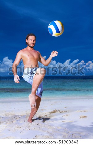 Handsome man is playing on the beach wearing fin - stock photo