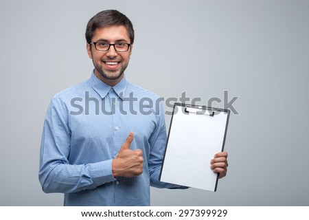 Handsome man is presenting a folder of papers. He is giving thumb up and smiling happily. Isolated on grey background and copy space in right side - stock photo