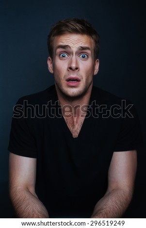 Handsome man is scared of what he has seen with black v-neck shirt on the black background - stock photo