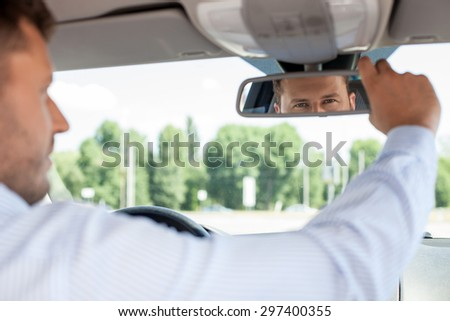 Handsome man is sitting at steering wheel. He is looking at mirror with attention and adjusting it - stock photo