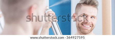 Handsome man is styling his hair with hairspray - stock photo