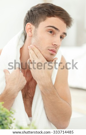 Handsome man is touching his chin in the bathroom. He is looking forward pensively and decided to shave. The man is carrying a white towel on his neck