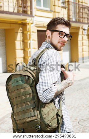 Handsome man is traveling on street. He is looking at the camera with interest. He is holding backpack on his shoulder and mobile phone - stock photo