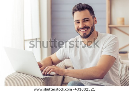 Handsome man is using a laptop, looking at camera and smiling while sitting on the sofa at home - stock photo