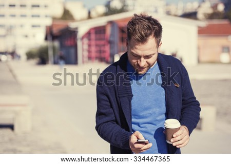 handsome man is using an application in his smartphone device sending a text message - stock photo