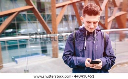 Handsome man is  using cell phone,   outdoor on the city street, Young attractive businessman, wearing casual blue shirt - stock photo