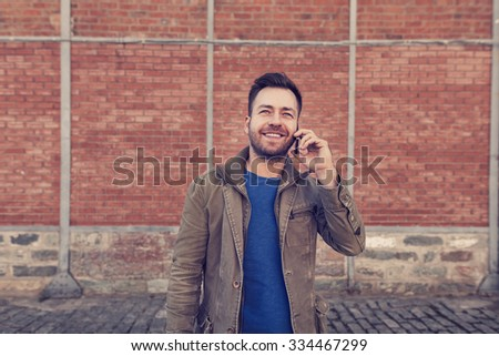 handsome man is using his smartphone device talking in front of a brick wall - stock photo