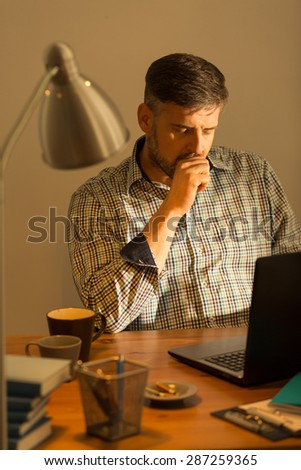 Handsome man is working on his computer on late hours - stock photo