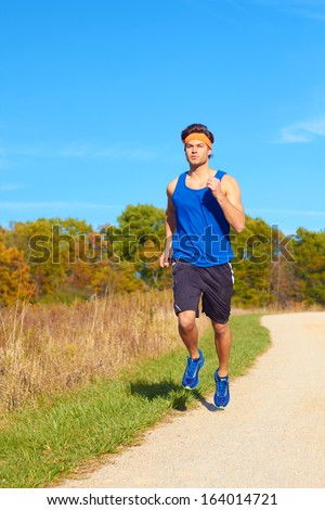 Handsome man jogging on nature trail near forest preserve. Color image, copy space, male jogger running outside on a beautiful day in nature.
