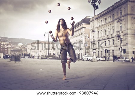 Handsome man juggling on a square
