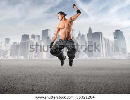 Handsome man jumping with cityscape on the background