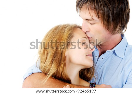 Handsome man kisses loving girlfriend on her forehead, isolated on white - stock photo