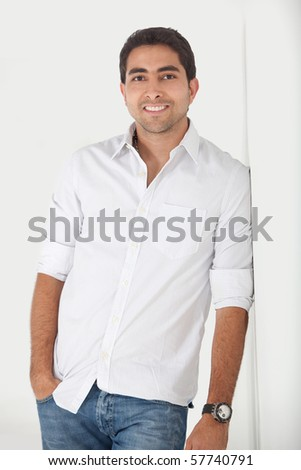 Handsome man leaning against a wall and smiling - stock photo