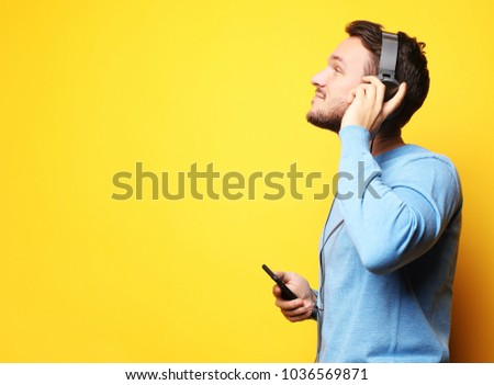 Handsome Man lictening to music over yellow background