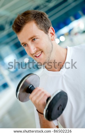 Handsome man lifting free weights at the gym - stock photo