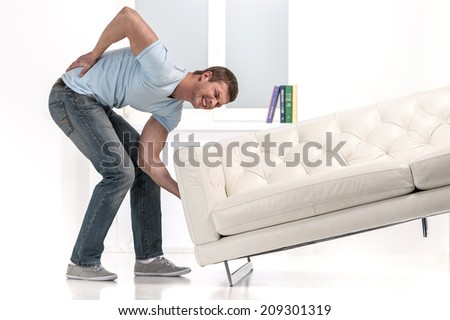 Handsome man lifting sofa and feeling pain. man droped sofa because of painful back - stock photo